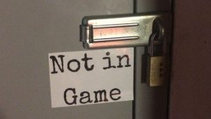 A sign reading NOT IN GAME by a door that is padlocked shut