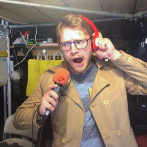 Man speaking in an orange microphone wearing orange headphones in LockHouse Escape Games foyer