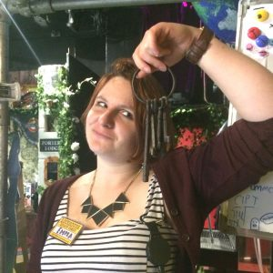 A woman holding up some old keys looking at them bemused in LockHouse Escape Games foyer