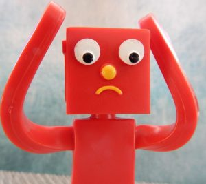 red robot toy looking confused with hands on his head in dismay