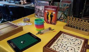 A collection of board games including Dobble, 7 Wonders, Codenames, Junk Art, Othello, Pick Up Sticks, and a rainbow slinky, arranged ready to play on a yellow foyer table