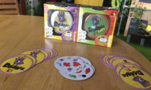 The board game Dobble on a table with colourful yellow and purple cards ready to play