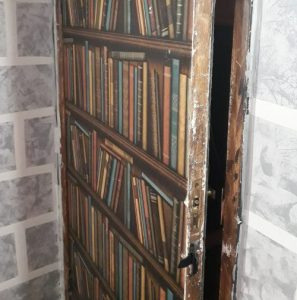 A secret door in a spy-themed escape room made to look like a bookcase, standing slightly ajar