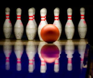 White and red bowling pins in a dark bowling alley about to be hit by a ball