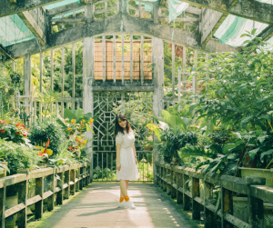 A woman standing in a green house with plants on shelves along each side of her. She is wearing a white dress