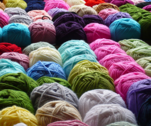 a collection of coloured balls of wool in a row