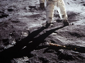 An astronaut suit from the waist down, casting a long humanoid shadow over the surface of the moon