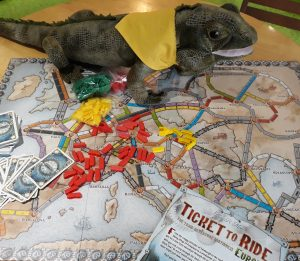The board game Ticket to Ride on a table, showing a map board and many small plastic game pieces and cards, with a green plush iguana soft toy next to it