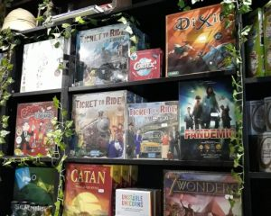 A shelf of board games including family board games Dixit, Ticket to Ride Europe, Pandemic, and Catan