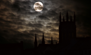 The moon shining through clouds over the misty silhouettes of buildings