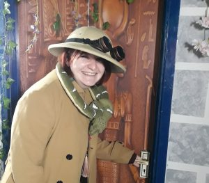 An excited looking person dressed up in an explorers hat and coat, with a snake draped around their neck, smiling widely as they open the door to an escape room