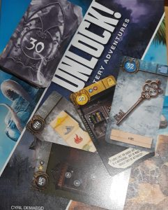 The box of the escape room board game Unlock, showing illustrated clue cards with a picture of a key