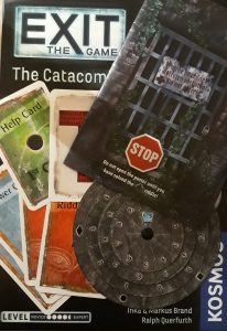 The escape room board game Exit, showing blue answer cards, orange riddle cards and green hint cards, as well as a code wheel and a folded poster