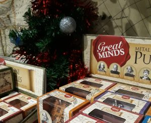 a selection of great minds puzzles with a christmas tree in the background