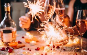 a christmas party table with hands holding glasses of champagne and sparklers