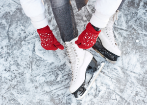 a view of a person in red mittens sitting on an ice rink tying the laces of ice skates