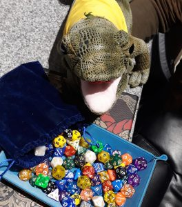 a blue dice tray containing many multicolored polyhedral dice on top of a dungeons and dragons rulebook, overlooked by a green soft toy lizard