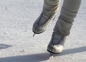 legs from the ankle down wearing white ice skates and skating on an ice rink