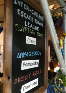 a blackboard recording the currently winning colleges for the cambridge student escape room league, with words in white reading inter-college escape room league, behind some metal scaffolding decorated with ivy and butterflies