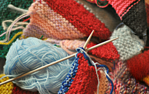 knitting needles with some multicoloured knitting on top of colorful blue and red yarn