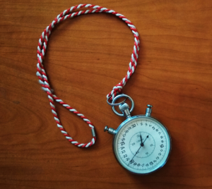 a stopwatch on a red and white string on a wood background