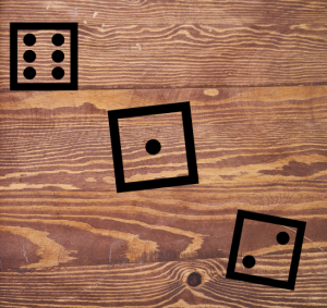 a wooden tabletop with the symbols of three dice on it in black font