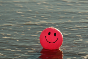 a red ball with a smiley face on it floating in the ocean