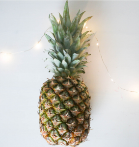 A pineapple on a soft white background with faint fairy lights surrounding it