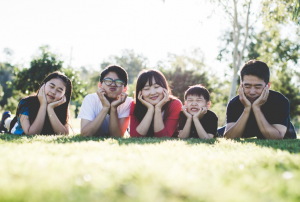 a family lying on grass smiling at the camera with their chins in their hands