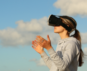a person wearing a vr headset holding their hands up in front of a background of blue sky with clouds