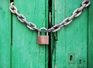 a padlock holding closed a chain in front of a green wooden door