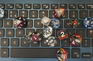 polyhedral dice for playing Dungeons and Dragons, some clear with blue streaks and some rainbow coloured, on top of a computer keyboard