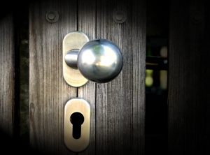 a wooden door with a silvery brass doorknob and keyhole slightly ajar