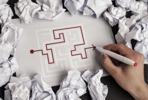 a paper maze puzzle with the route drawn in red pen by a hand, surrounded by crumpled paper