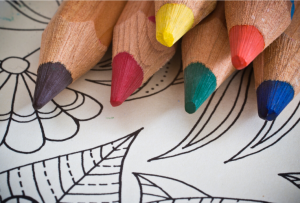 a selection of multi coloured colouring pencils on top of a white colouring page