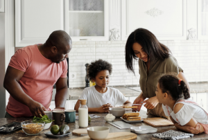 a family with two parents and two children around a table with cooking ingredients
