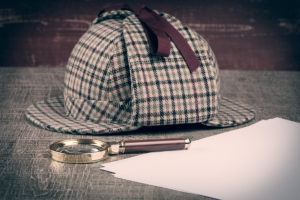 a deerstalker beside a magnifying glass and some sheets of blank paper