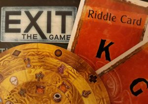 the box of an exit game, showing two orange riddle cards and a golden card decoder disk