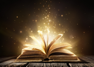 a story book lying open on its spine with golden light coming out of it