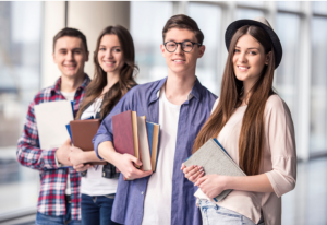 a group of students holding books and folders smiling at the camera